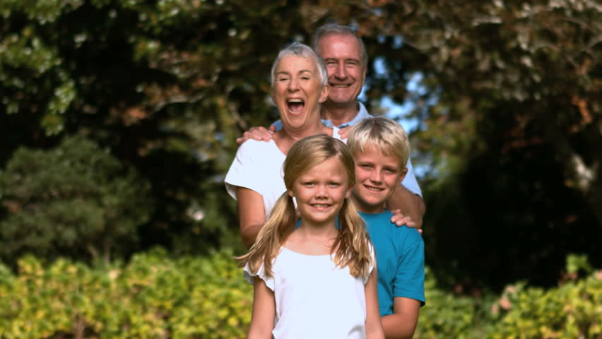 Cheerful multi-generation family posing in a park in slow motion