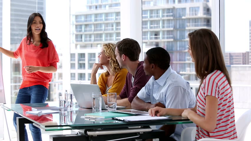 Woman giving presentation to her colleagues during a meeting | Shutterstock HD Video #4227691