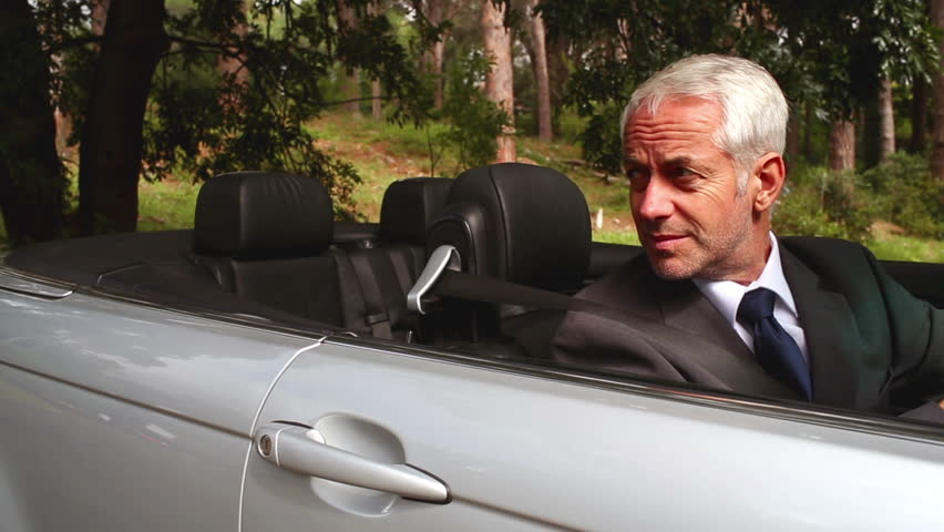 Confused businessman looking at map in his convertible car