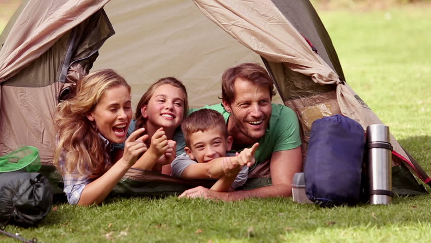 Young family lying in their tent observing something funny