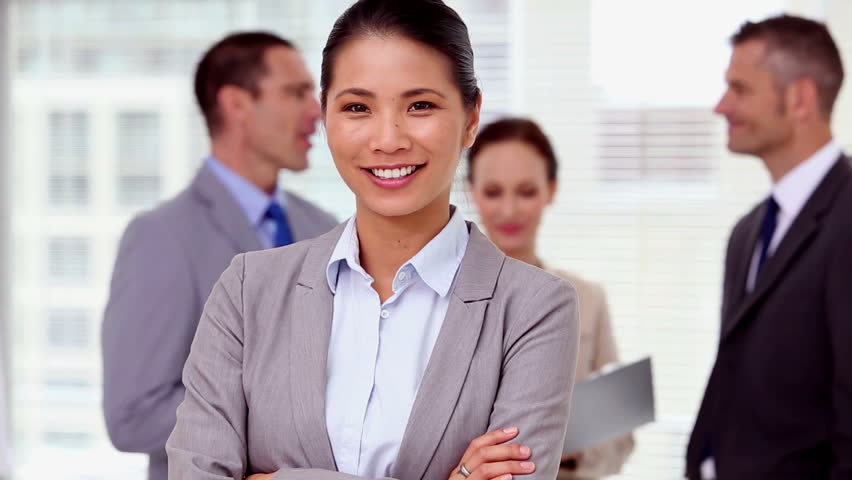 Businesswoman laughing and looking at camera while colleagues are discussing behind | Shutterstock HD Video #4229077