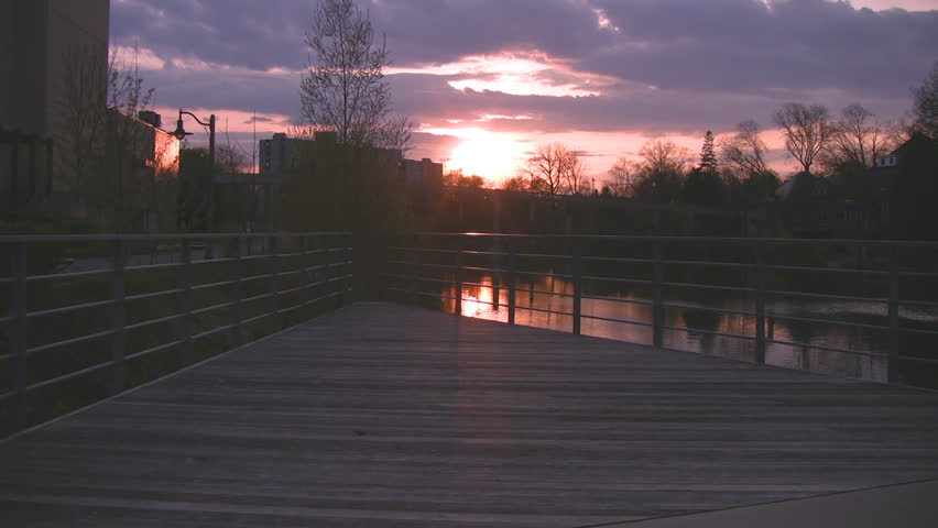 A view over a boardwalk with a setting sun in the distance.  The shimmering water of the Speed River in Guelph, Ontario, Canada, is also visible.