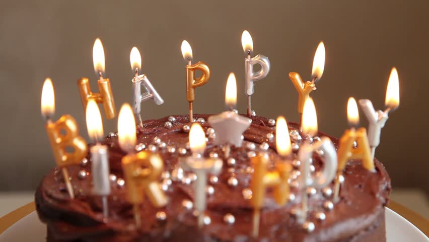 Stock Video Clip of A chocolate birthday cake with candles