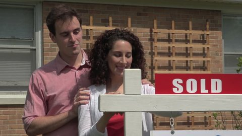 Real Estate, couple standing in front of sold sign