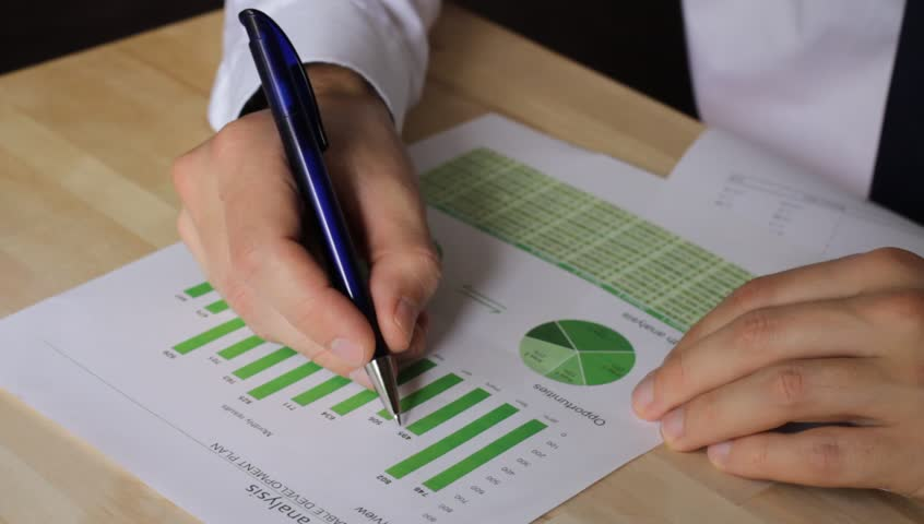 Businessman analyzing sustainable development opportunities charts at workplace. Hand holding a pen and green charts.   Shutterstock HD Video #4272395
