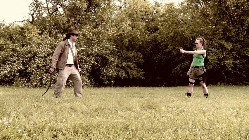 Male and female adventurers fight with whip and gun on grassland in front of