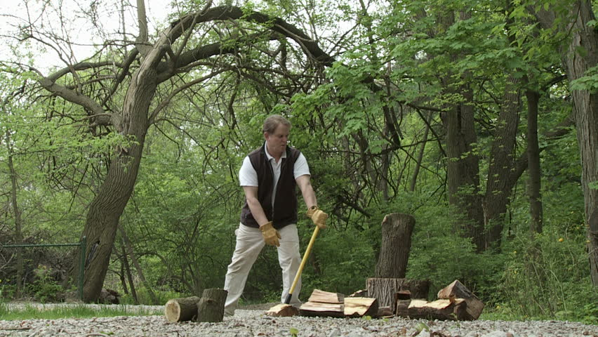 Man chopping up logs with an axe.  Overcranked slow motion.  Background of woodland.  Wide side view. #4292675