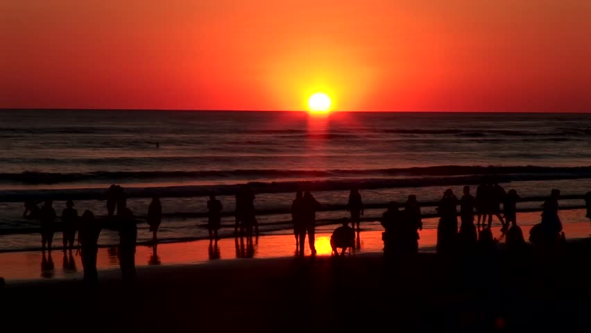 Silhouettes of people on the sand and in the surf watching a beautiful sunset on the west coast of Florida.