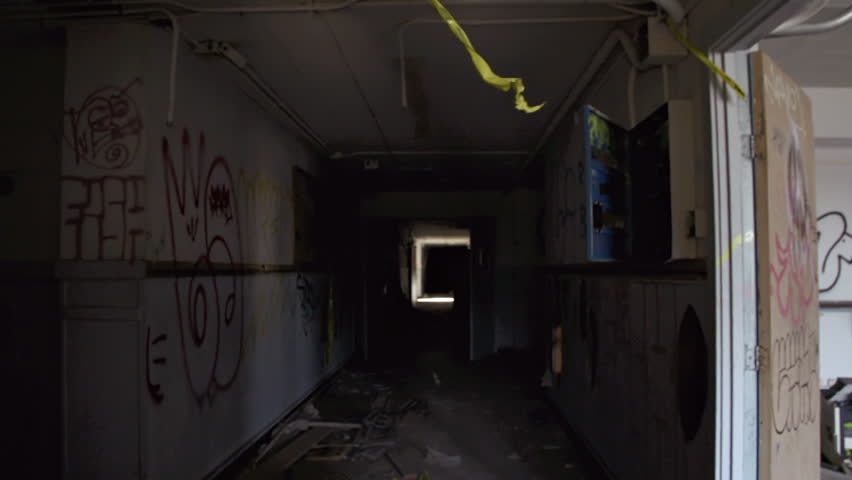 Handheld POV shot in hallway of a derelict abandoned urban building