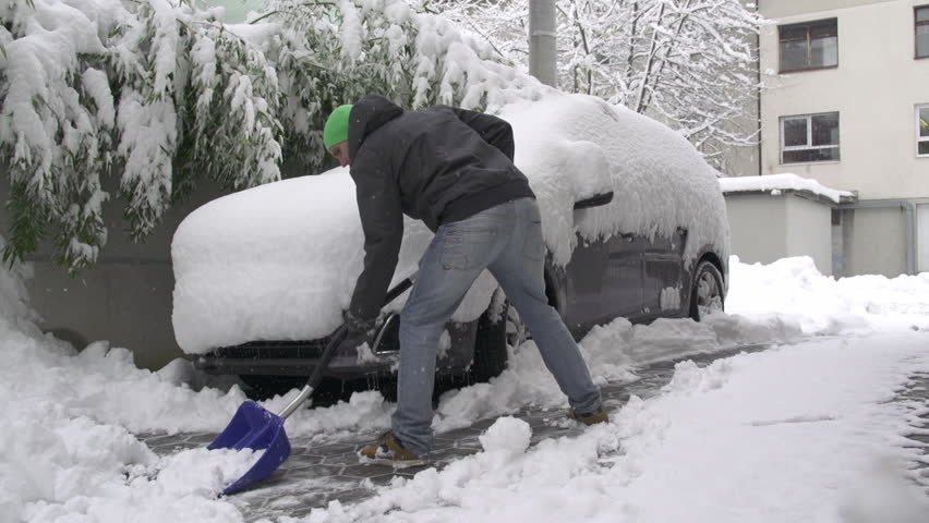 Man shoveling snow in front of his car