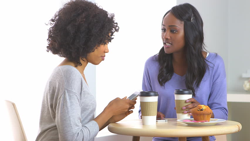 African American friends texting with mobile phone in caf\x8E | Shutterstock HD Video #4338365