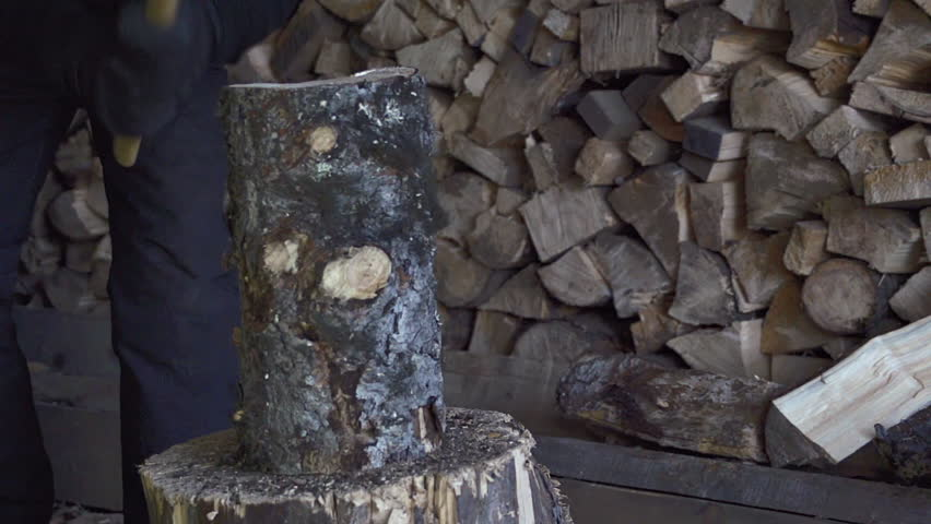 Man in snow pants splits a cord of firewood with an ax in slow motion
