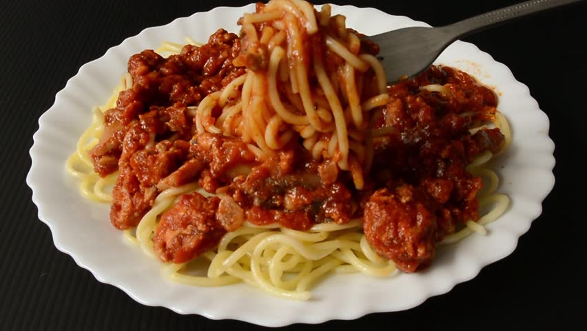 Fresh boiled Italian spaghetti pasta cuisine food with chicken tomato sauce is ready to eat with fork in black isolation background