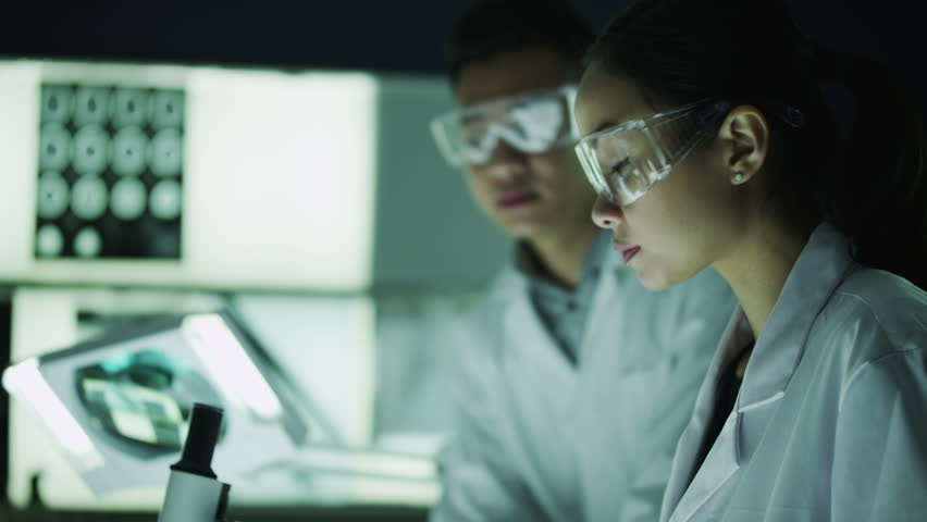 Two young Asian scientists or medical researchers working in a dark laboratory together.