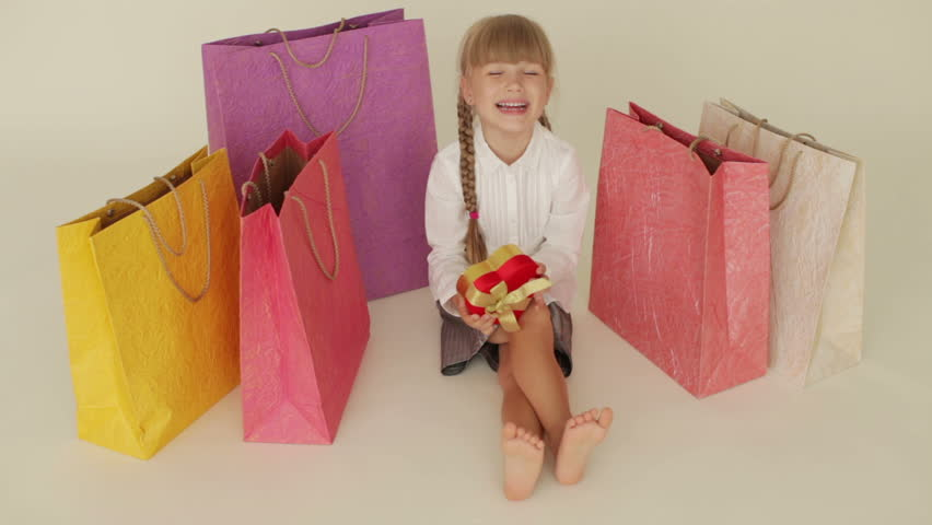 Funny little girl sitting on floor surrounded by shopping bags holding