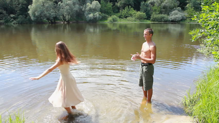 A love story. A man and a woman beautiful couple near the water on the shore of the rivers. Love and kisses.