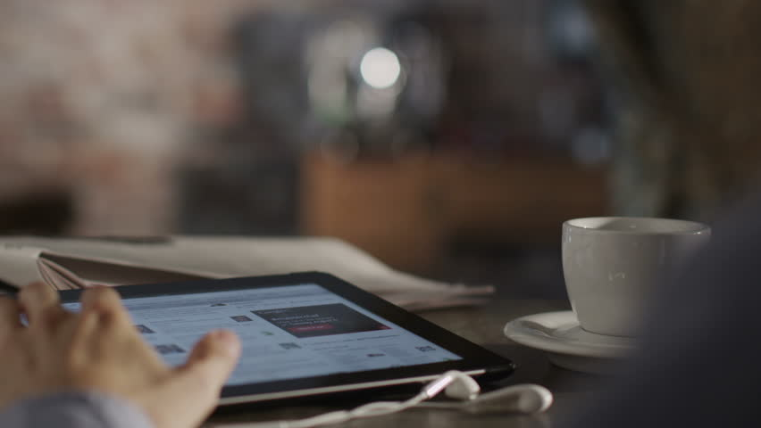 Man Reading News with Digital Tablet and Drink Coffee. Shot on RED Digital Cinema Camera in 4K (ultra-high definition (UHD)), so you can easily crop, rotate and zoom, without losing quality! | Shutterstock HD Video #4375256