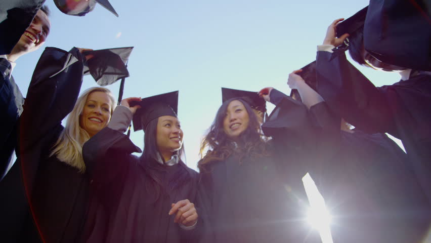 Graduation caps are tossed into the air by a happy group of friends on a bright sunny day. In slow motion. with flare. | Shutterstock HD Video #4375850