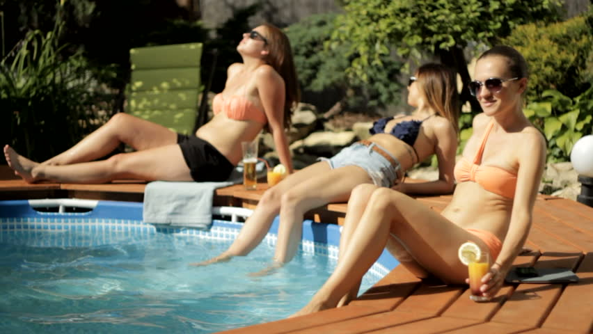 Girls taking sunbath by the pool