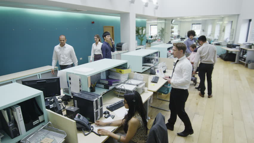 Attractive young multi ethnic group working together as a team in a busy modern office or call center. In slow motion.