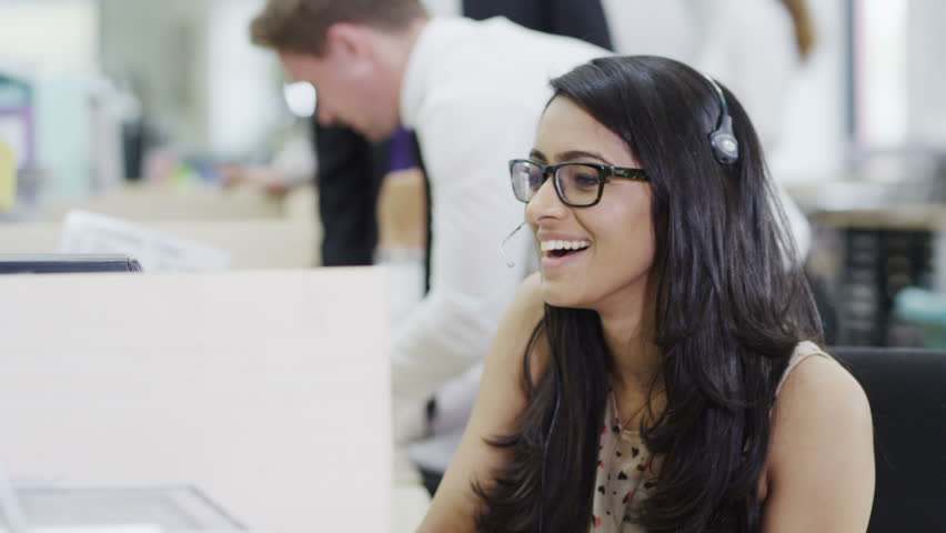 Cheerful young customer service operator, at work in a busy call center | Shutterstock HD Video #4390568