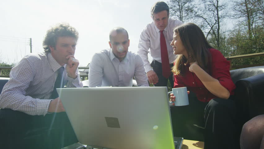 Business group come together for a casual outdoor meeting on a bright sunny day. They are on a terrace adjoining their office, surrounded by natural landscape. In slow motion.