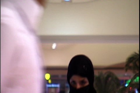 RIYADH, SAUDI ARABIA - SEPTEMBER 25, 2002: Woman in black niqab using cell phone as she gets off the escalator.