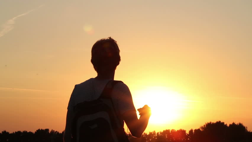 Backpack traveler enjoys dusk, after climbing up mountain