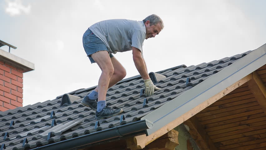 Pulling Out Broken Roof Tiles And Throwing Away. Destroyed roof tiles on completely new house with no facade and no insurance yet. Man changes broken tiles because of hail storm destroyed the roof.