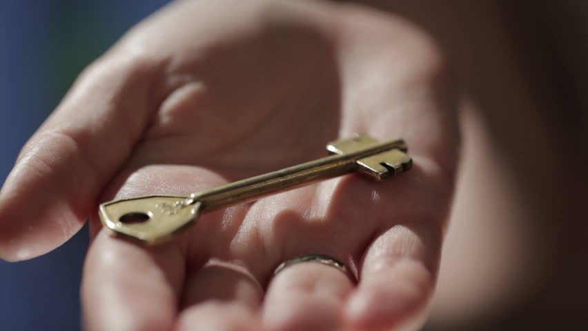 Woman hand with a wedding ring holding a key. Close up detail.