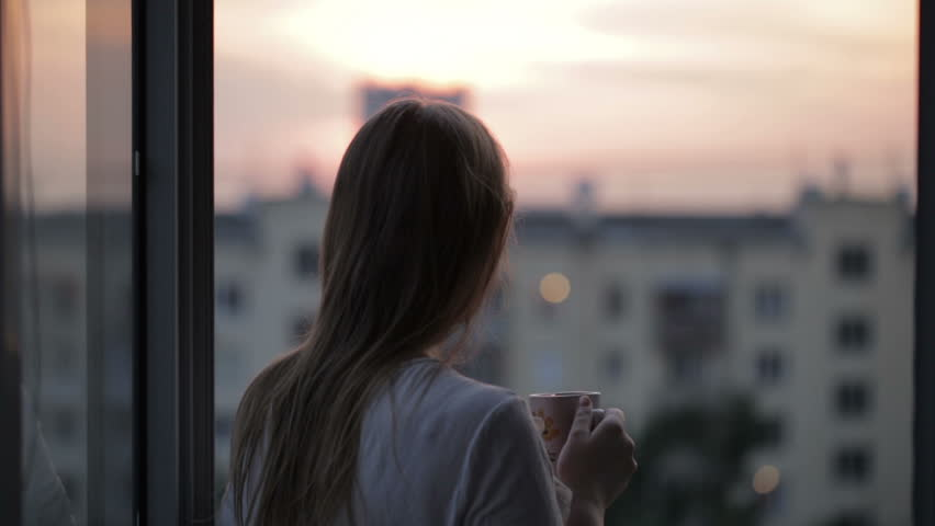Young girl on the balcony watching the sunset and drinking tea. Middle shot