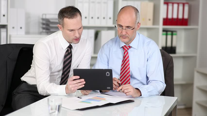 Businessmen sitting together at a table in the office reading information on a handheld tablet-pc screen | Shutterstock HD Video #4423385