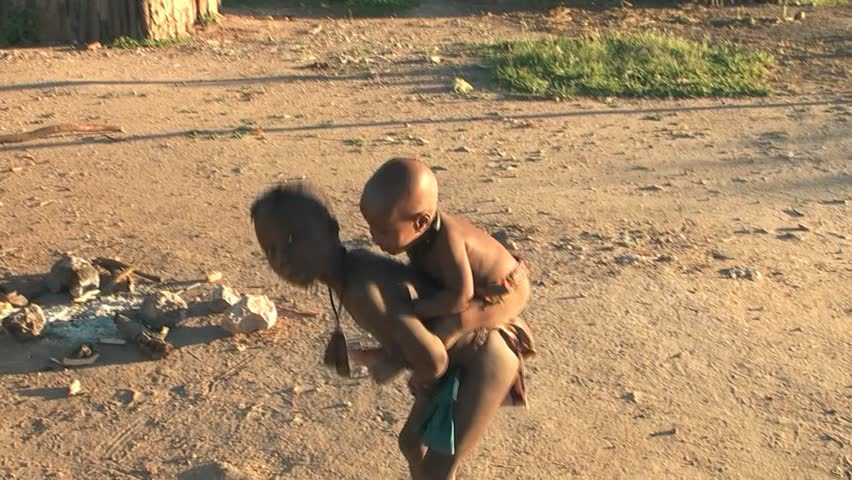 KAMANJAB - MARCH 28:  African native tribes - Young Himba boy carries his sister on his back on March 28, 2012 in Kamanjab, Namibia.
