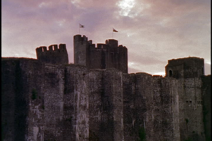 Towers with flags waving peek over high stone walls of Caerphilly Castle in Caerphilly, South Wales.