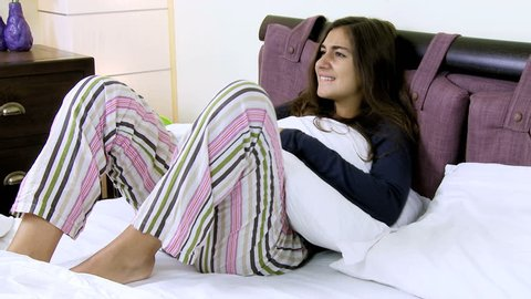 Young woman with menstrual pain laying in bed