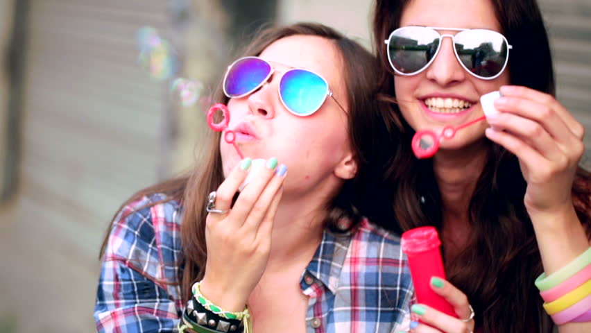 Two friends in hipster outfit having fun blowing bubbles in city