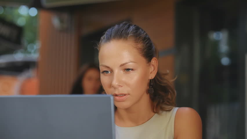 An attractive woman sitting in a cafe and working on the computer. It looks very puzzled and a little sad, it something does not work in