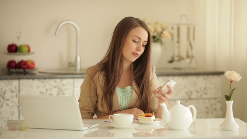 Pretty Girl Sitting At Kitchen Table With Cup Of Tea Using Mobile ...