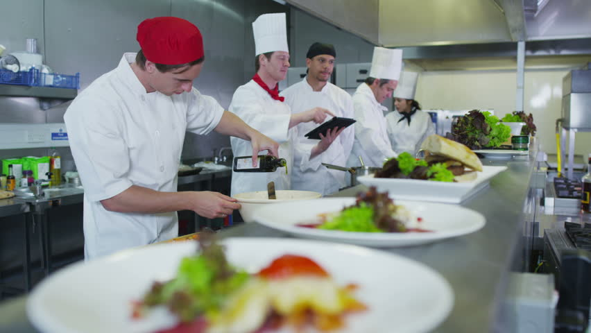 Professional chefs in a restaurant or hotel kitchen. They are looking at a digital tablet and organizing their menu and work schedule.