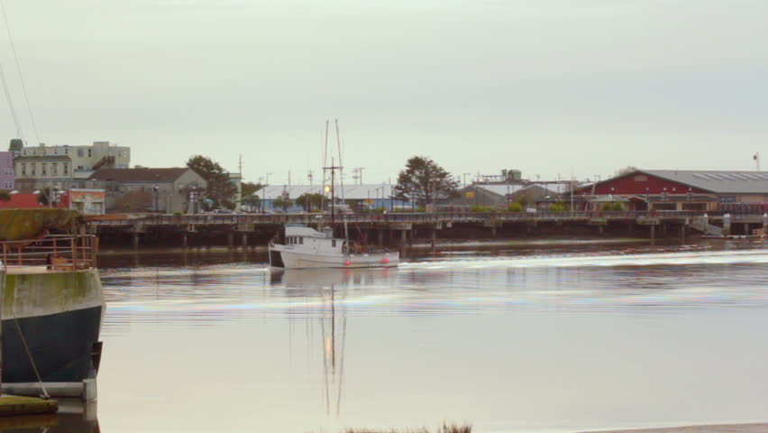 A boat pulls slowly into a harbor on a relatively overcast day. THe harbor is located in Humboldt Bay.  #4458815