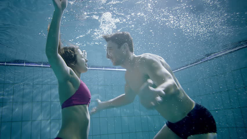 Attractive and playful couple underwater kissing and embracing.