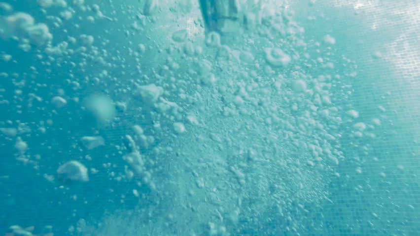 Bubbles rising to the surface. Slow motion. Air bubbles in clear blue water in pool (underwater shot), good for backgrounds