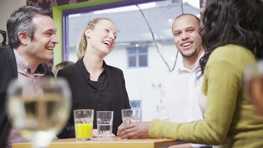 Happy group of friends or business colleagues chatting and laughing together in a small cafe or wine bar.