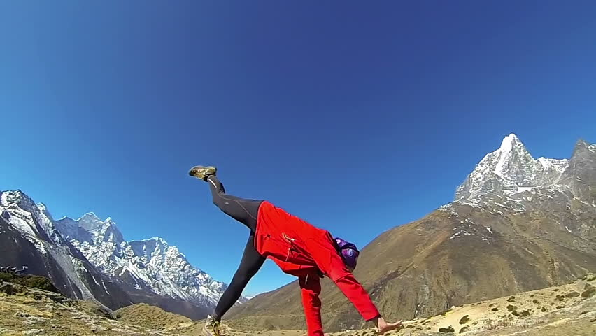 Happy woman doing the cartwheel on the top of the world, Mount Everest,Himalayas .Slow motion,high speed camera