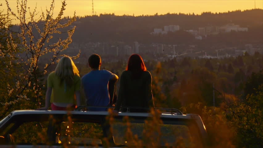 3 Teens Sit On Car And Watch The Sunset
