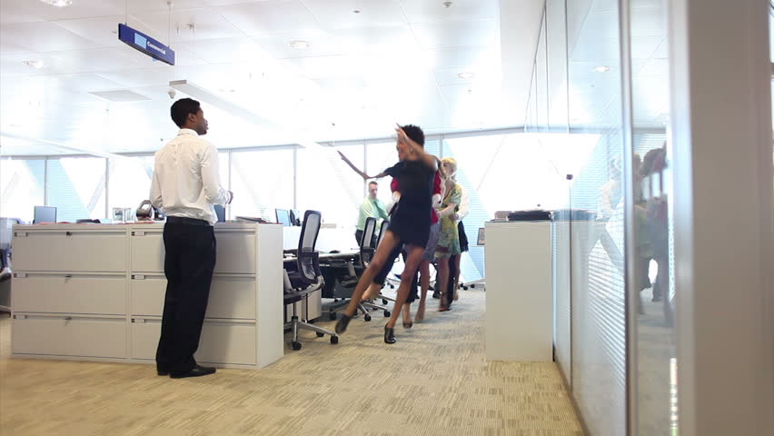 Funny group of business people dancing in large corporate offices. Man joins the crowd.