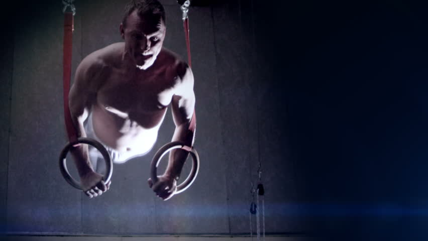 Male gymnast performing routine on gymnastic rings. Olympics sport in contemporary setting. Slow motion Shot on RED Epic at 240FPS | Shutterstock HD Video #4495715