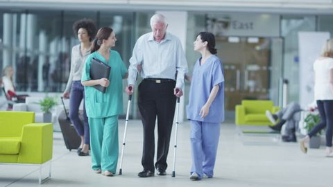 Man comforted by caring medical staff. Assisting people when life throws unexpected obstacles in your way. A hospital ward or waiting area where patients can by seen by doctors and nursing staff.