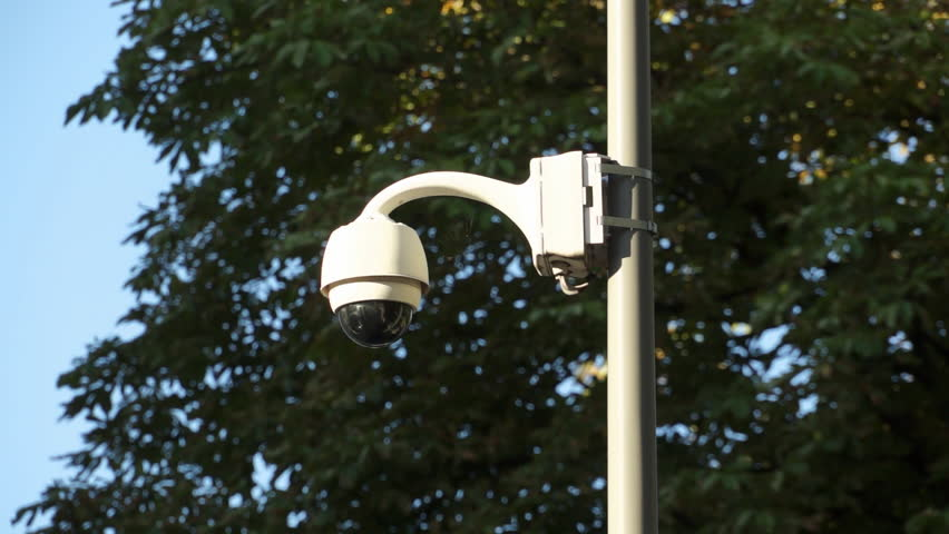 White security camera outside on pole. Surveillance dome cctv camera in streets shots direct to camera.