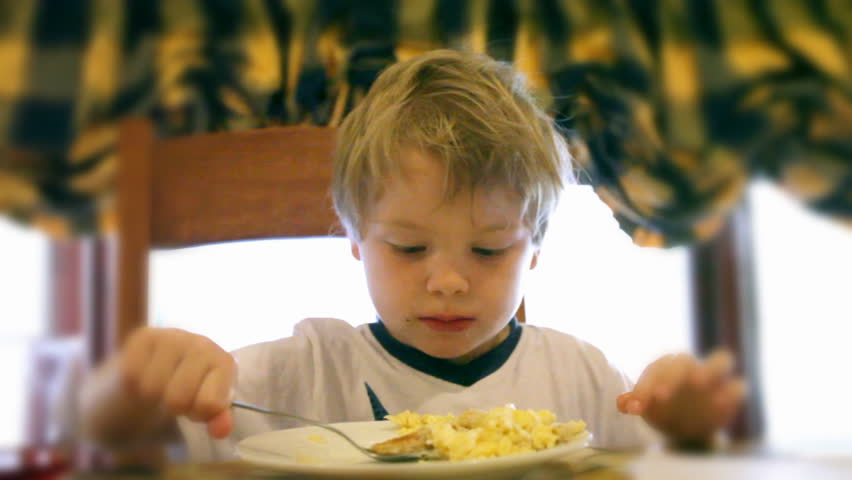 Little boy eats scrambled eggs
